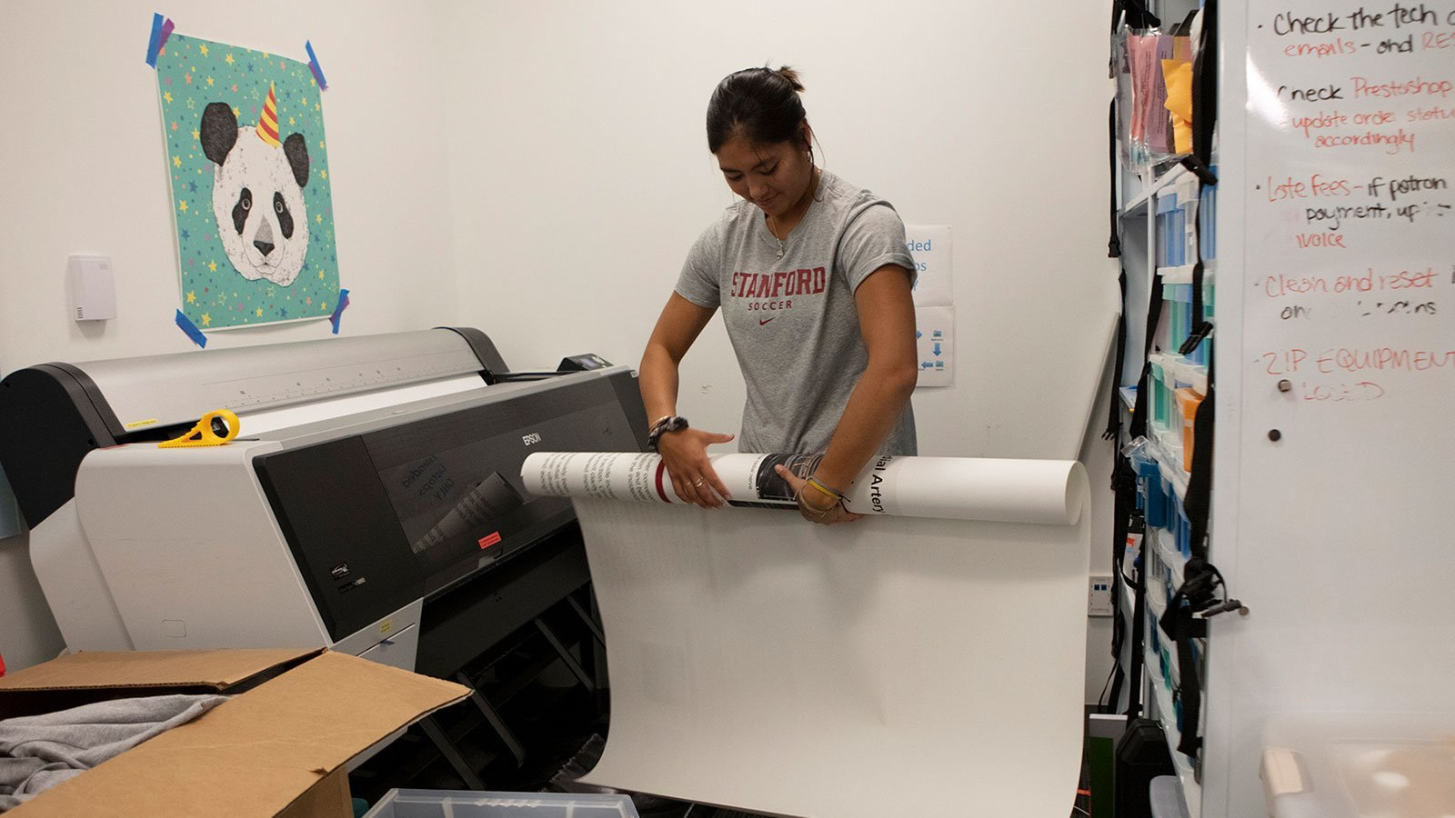 Student rolling up a poster near a printer